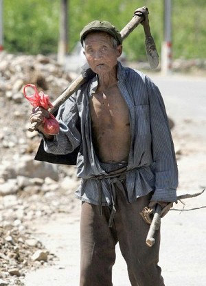 Chinese farmer with a traditional hoe. Notice he is not fat.