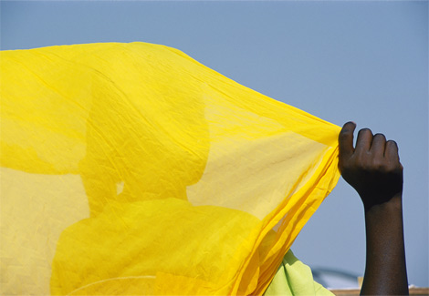 A woman in Diafarabe, Mali, holds her brilliant yellow scarf against a deep blue African sky.