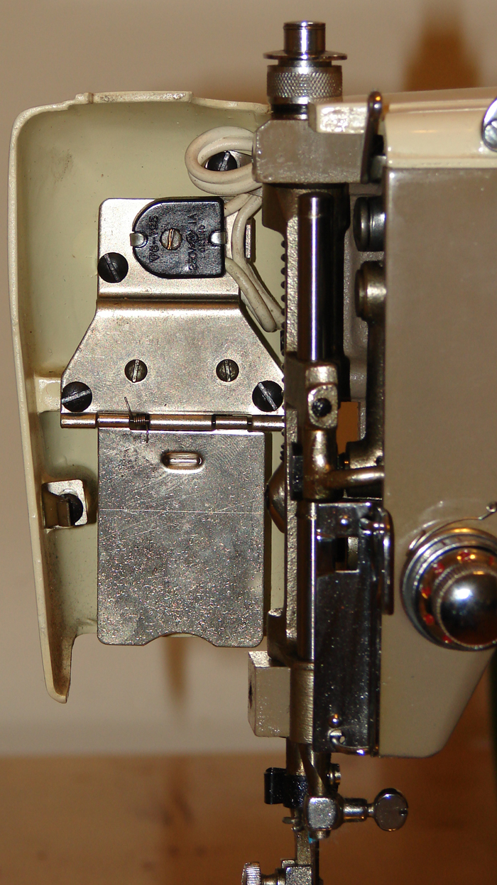 Imperial sewing machine, model 535: Front cover light. The head swivels open, revealing the heat shield and the bulb underneath. The head does heat up when the light is on.