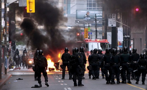 Toronto riot police look on as fire department put out a burning police car