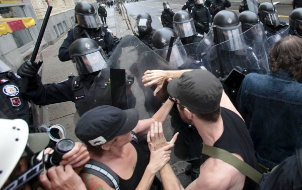 Toronto riot police push protesters back