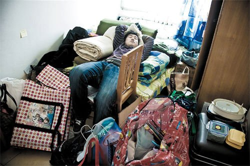 Di Qun, one of the ants in Tangjialing, China rests in his cramped room.