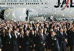 New recruits at Japan Airlines Corp. toss paper planes at a hangar at Tokyo's Haneda airport during the bankrupt carrier's ceremony to welcome them Thursday.