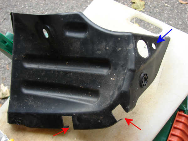 2016 Honda Fit: rear right splash guard install. Cover top is on the left. Drill out one hole (blue arrow) and two cutout tabs (red arrow). Photo by Don Tai