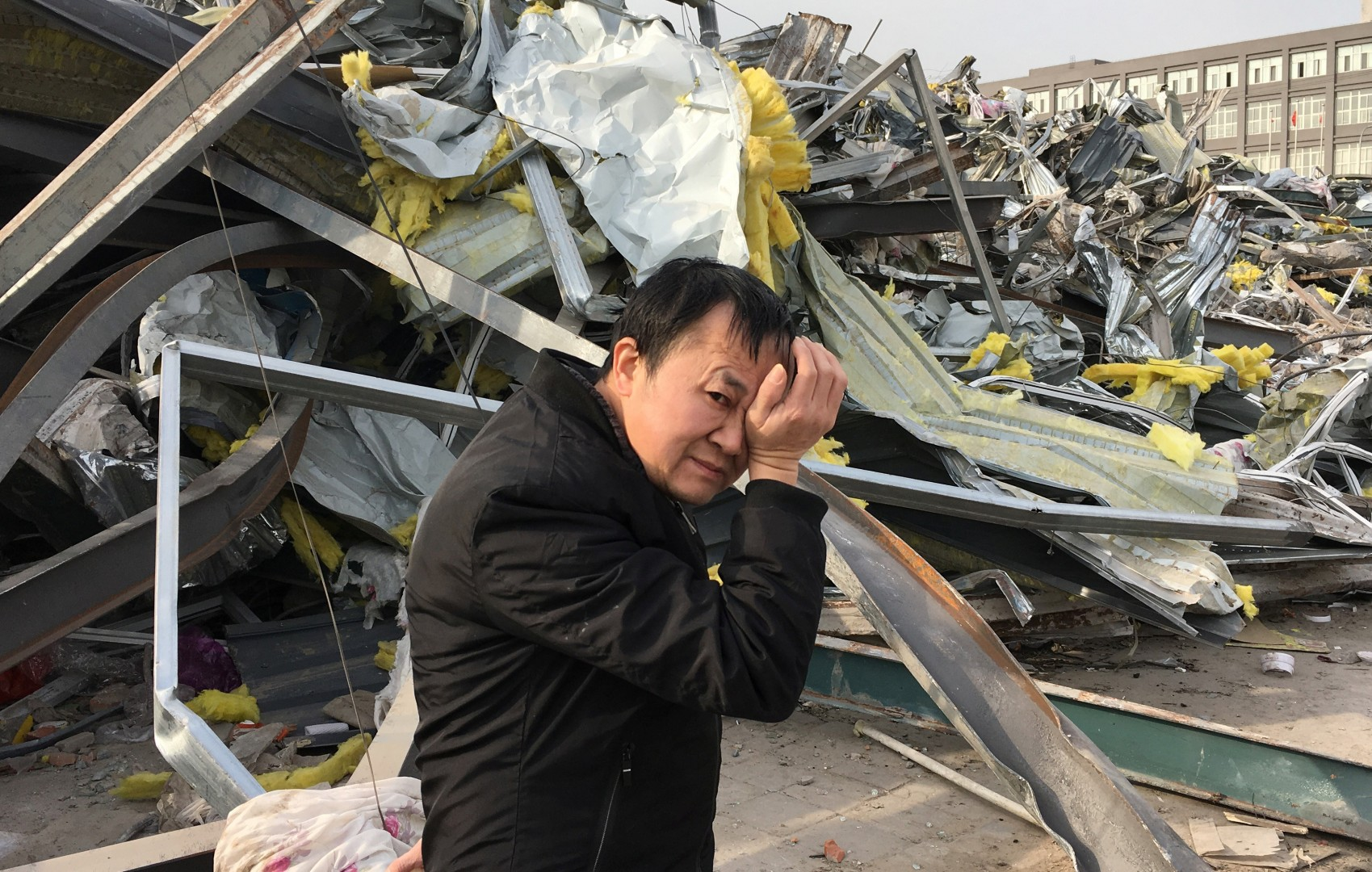 China, Beijing, Daxing, Xinjian Cun, where the government has destroyed the neighborhood of migrant workers and evicted everyone. I feel really sorry for this guy, who is obviously upset. Note the building in the background. Reuters